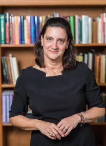 Suzanne Akbari in a black dress, standing in front of a bookshelf